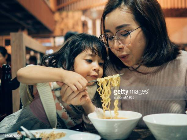 young asian woman and her daughter enjoying in korea restaurant. - korean culture stock pictures, royalty-free photos & images