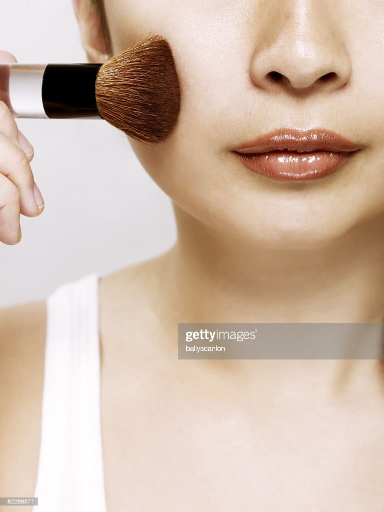 Young asian woman applying makeup with a brush : Stock Photo