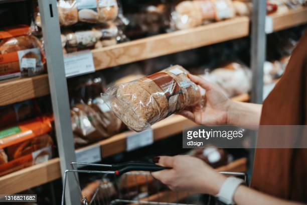 young asian woman carrying a shopping basket grocery shopping in a supermarket, shopping for packaged fresh wholegrain bread in the bread aisle. healthy eating lifestyle - gluten free bread stock pictures, royalty-free photos & images