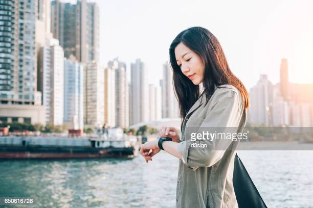 Young Asian woman checking her smart watch by the harbour in city against urban skyline