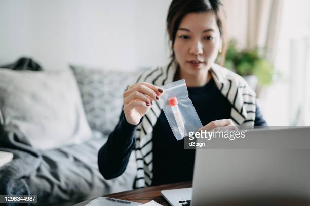 young asian woman consulting to her family doctor online in a virtual appointment, holding a medical test tube, conducting covid-19 diagnostic test at home - 唾液検査 ストックフォトと画像