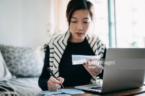 young asian woman consulting to her family doctor online in a virtual appointment, holding a medical test tube while filling in the laboratory form, conducting covid-19 diagnostic test at home - 唾液検査 ストックフォトと画像