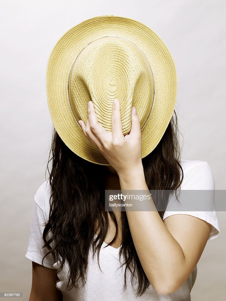 Young asian woman covering face with a straw hat : Stock Photo