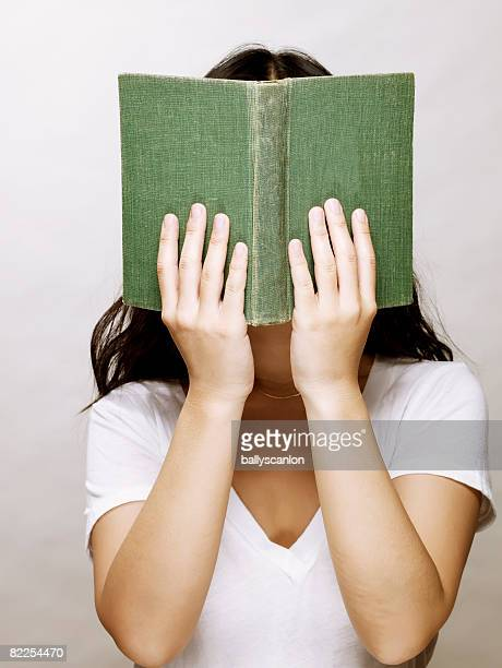 Young asian woman coveringh her face reading book