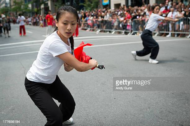 Young Asian woman demonstrates her proficiency with a sword during a parade. The shot was taken in close proximity with a wide angle lens on a sunny...