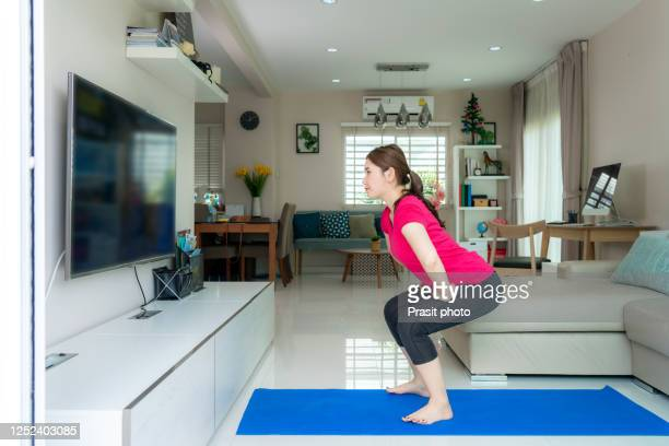 young asian woman doing squats training together and looking tv at home and working out standing in living room, fit pair performing fitness exercise during self-quarantine - crouching stock pictures, royalty-free photos & images