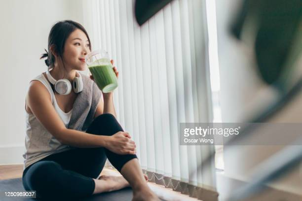 young asian woman drinking green smoothie after yoga - active lifestyle stock pictures, royalty-free photos & images