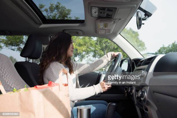 young asian woman driving a car after shopping - vehicle interior stock pictures, royalty-free photos & images