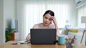 Young asian woman employee work from home using computer notebook videocall meeting conference angry annoy with low poor unreliable internet wifi connection problem issue outage.