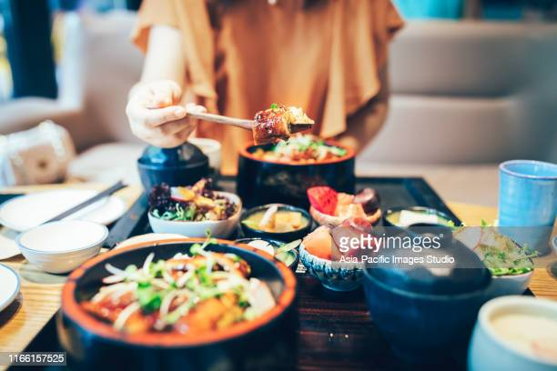 young asian woman enjoying japanese food-eel rice. - japanese food stock pictures, royalty-free photos & images