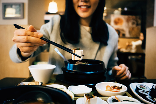Young Asian woman enjoying Korean meal and eating with chopsticks in a Korean restaurant - gettyimageskorea