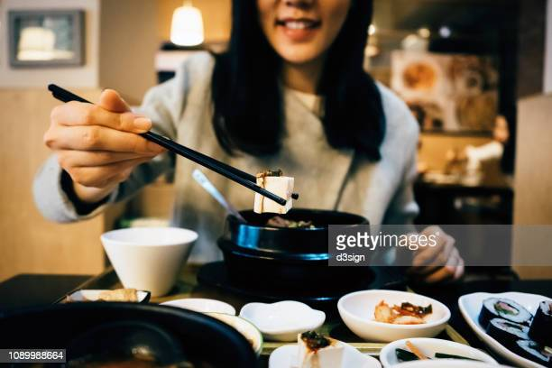 young asian woman enjoying korean meal and eating with chopsticks in a korean restaurant - korean food stock pictures, royalty-free photos & images