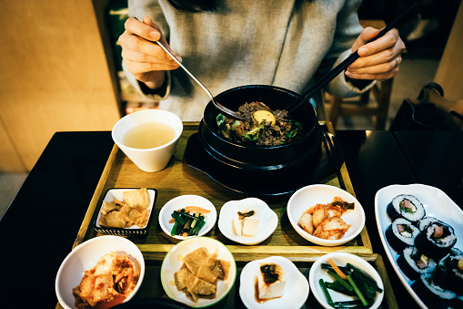 Young Asian woman enjoying Korean meal in a Korean restaurant - gettyimageskorea