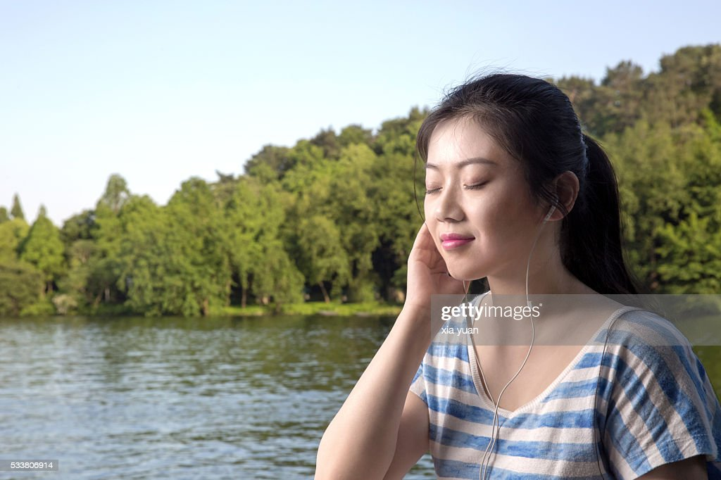 Young asian woman enjoying listening to music on lakeshore,with eyes closed : Foto stock