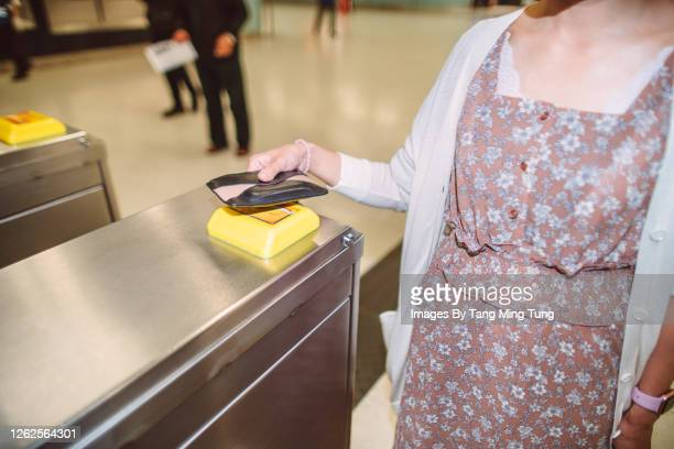 young asian woman entering a turnstile with smart card at train station - 改札 ストックフォトと画像