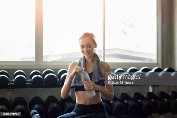 young asian woman exercise with dumbbell at fitness gym.healthy lifesyle concept. - asian six pack stock photos and pictures