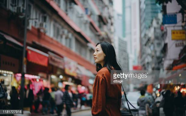 young asian woman exploring and strolling in local street market in hong kong - city break stock pictures, royalty-free photos & images