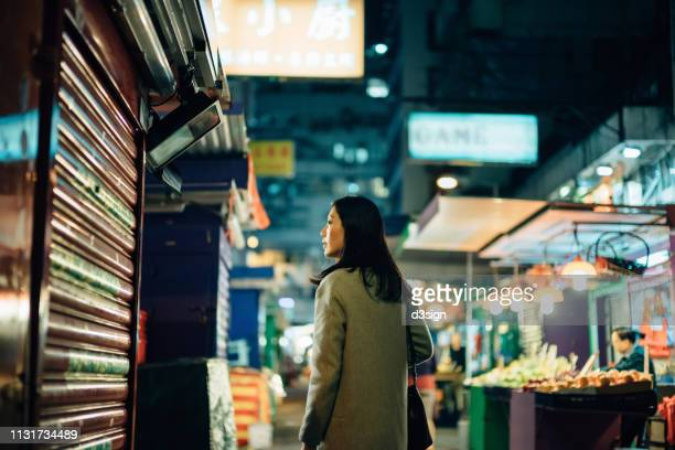 young asian woman exploring and strolling in local street market in hong kong at night - one night stand stock-fotos und bilder