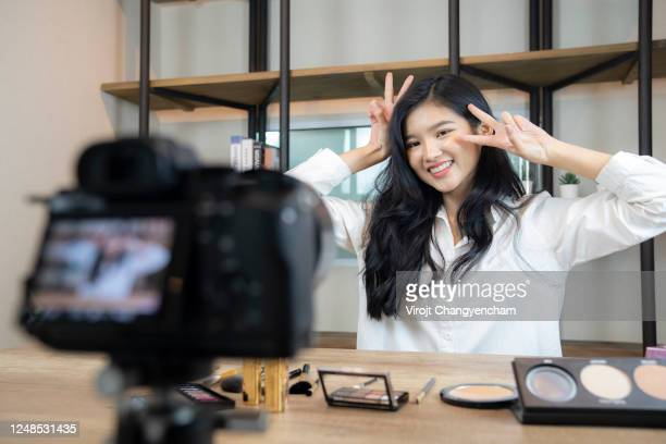young asian woman fashion vlogger trying live streaming online with digital camera at home - live broadcast stock pictures, royalty-free photos & images
