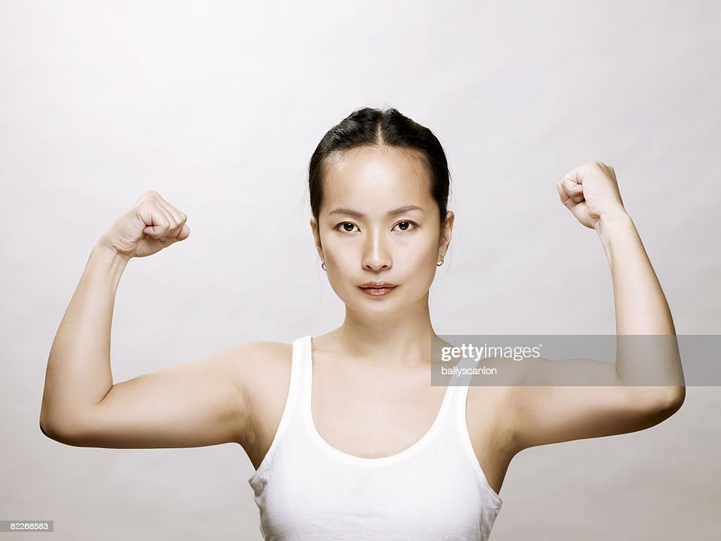 Young asian woman flexing her muscles : Stock Photo