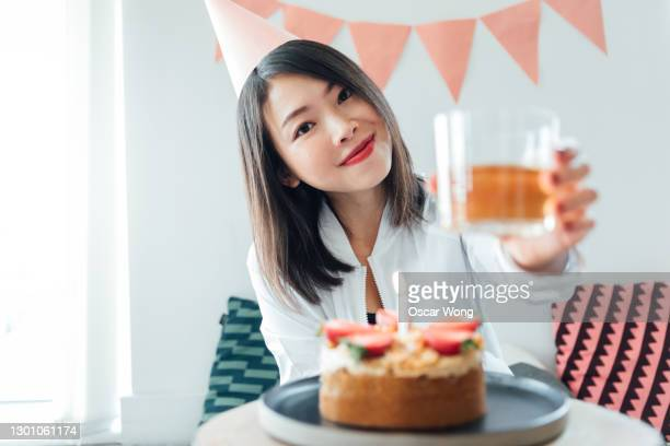 young asian woman giving a toast in front of her birthday - live broadcast stock pictures, royalty-free photos & images