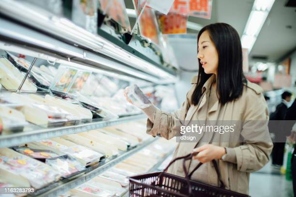 young asian woman grocery shopping and choosing fresh poultry in supermarket - quedarse en casa frase fotografías e imágenes de stock