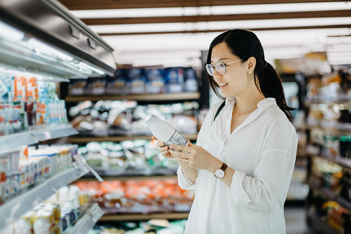 Young Asian woman grocery shopping in supermarket and holding a bottle of fresh milk - gettyimageskorea