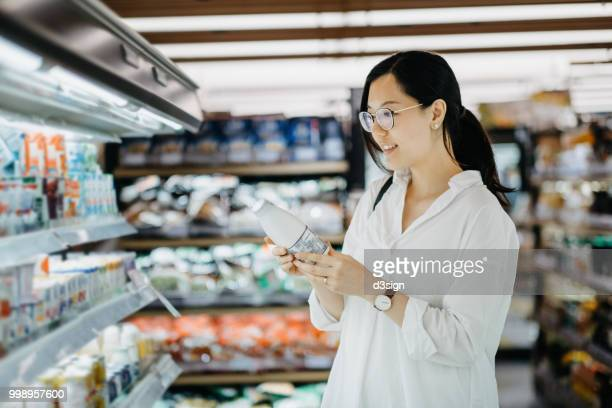 young asian woman grocery shopping in supermarket and holding a bottle of fresh milk - asian drink stock photos and pictures