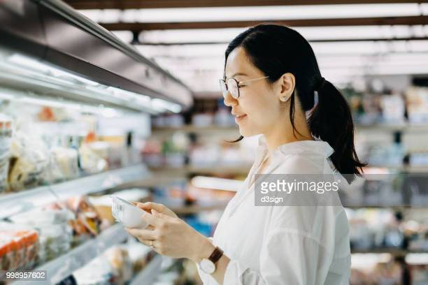 young asian woman grocery shopping in supermarket and reading nutrition label on a packet of fresh egg - convenience store stock photos and pictures