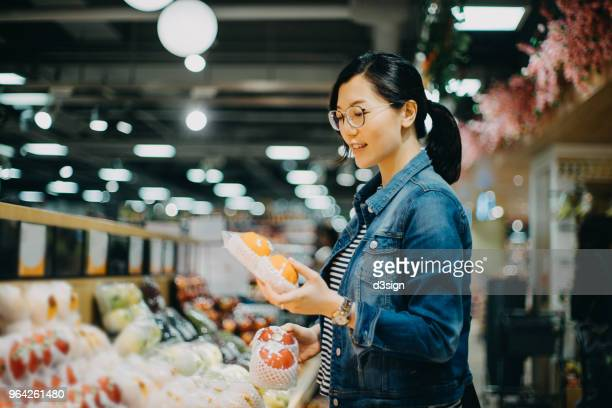 young asian woman grocery shopping in supermarket choosing fresh organic fruits - convenience store stock photos and pictures