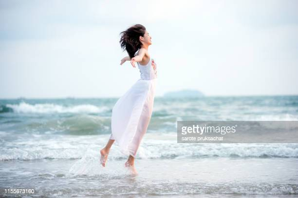 young asian woman happiness and feeling freedom on the beach . freedom concept. - 白い服 ストックフォトと画像