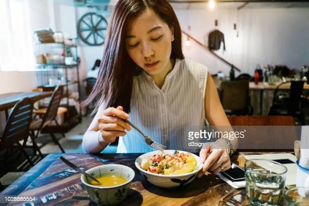 young asian woman having healthy green salad and soup in restaurant - servierfertig stock-fotos und bilder