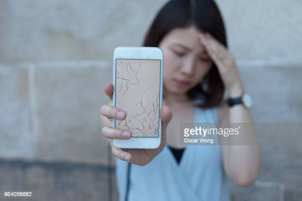 Young Asian woman holding broken phone