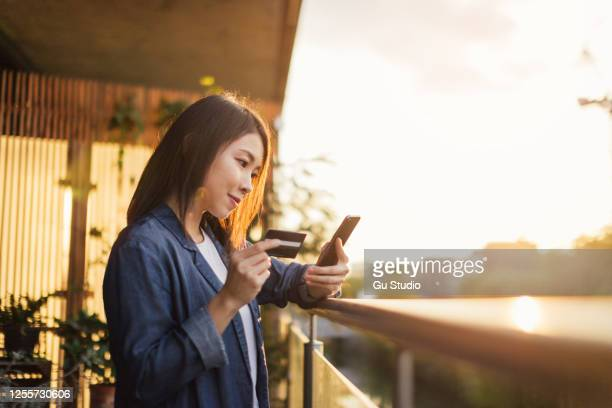 young asian woman holding credit card while using mobile phone for online shopping at balcony - consumerism stock pictures, royalty-free photos & images
