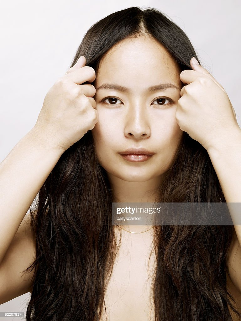 young asian woman holding hair back from her face : Stock Photo