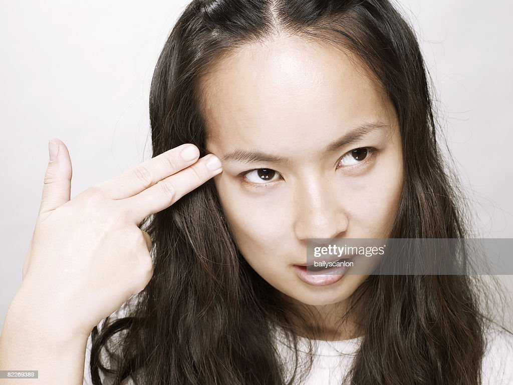 Young asian woman holding hand to her head : Stock Photo