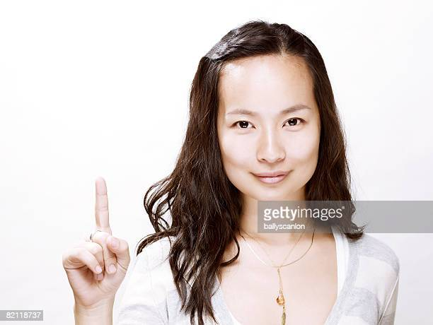 Young asian woman holding her finger up