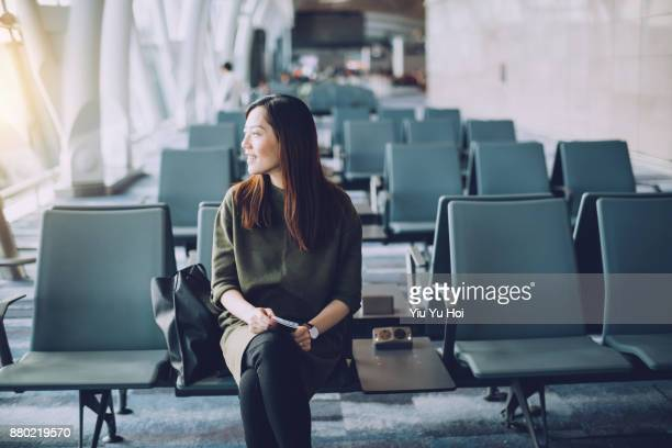 Young Asian woman holding passport and boarding pass on hand waiting in the departure lounge in airport