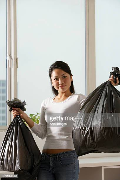 Young Asian woman holding up trash bags