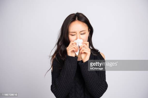a young asian woman in a black sweater blew her nose - sneezing stock pictures, royalty-free photos & images