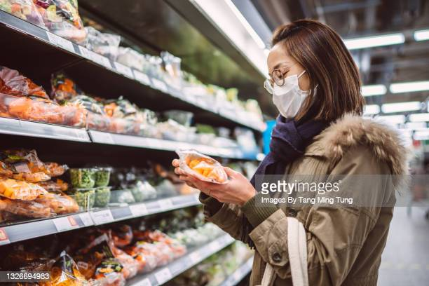 young asian woman in protective face mask doing grocery shopping for fresh vegetables in supermarket - organic stock pictures, royalty-free photos & images