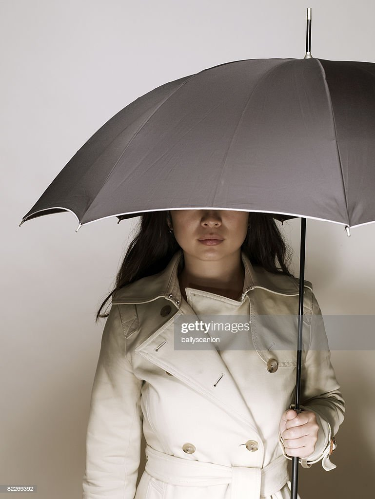 Young asian woman in raincoat, holding umbrella : Stock Photo