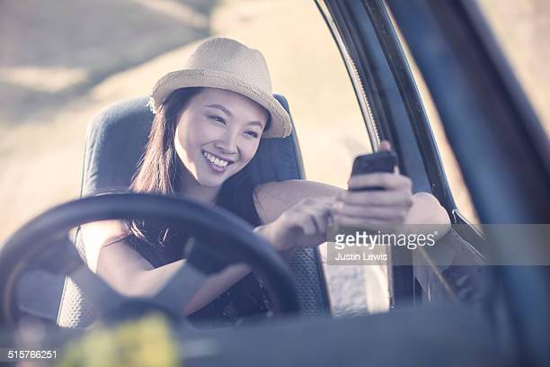 Young Asian woman in ranch truck smiling, texting