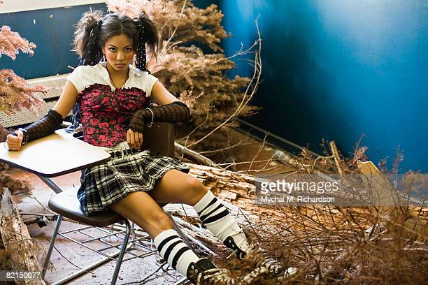 Young Asian woman in school desk next to dead trees