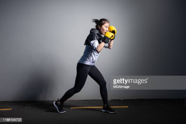 a young asian woman in sportswear is exercising - women's boxing stock pictures, royalty-free photos & images