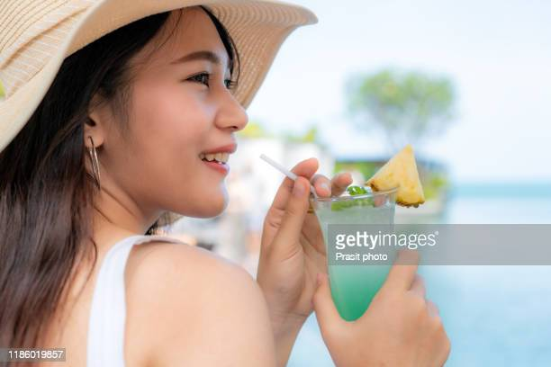 young asian woman in white dress with cocktail on the beach enjoying sunny weather looking on the ocean view. tropical paradise getaway travel vacation tourism concept. - 白のドレス ストックフォトと画像