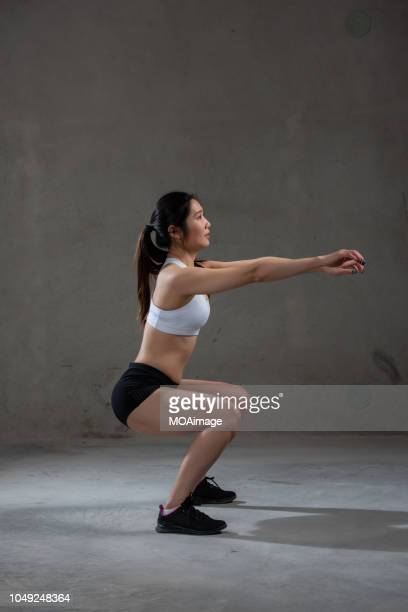 a young asian woman is doing stretching training - crouching stock pictures, royalty-free photos & images