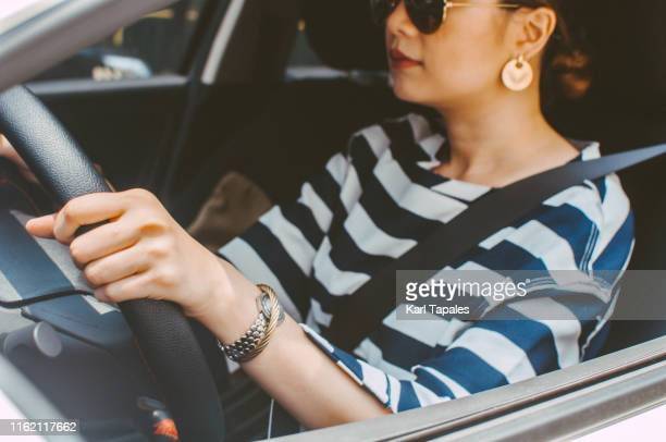 A young Asian woman is driving a car daytime