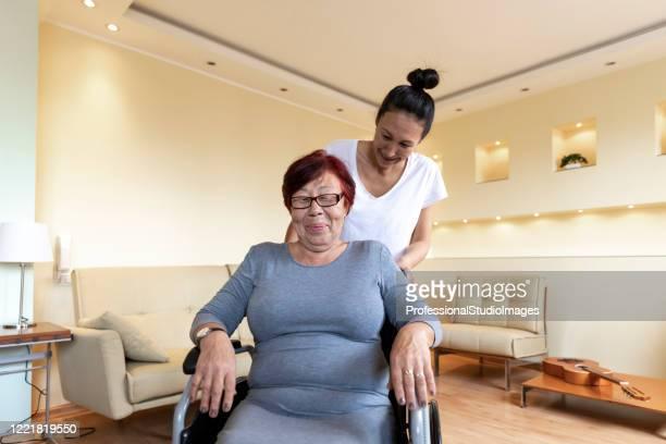 a jovem asiática está ajudando uma idosa com deficiência física. - assistente social - fotografias e filmes do acervo