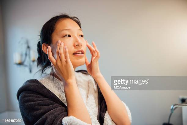 a young asian woman is washing her face - washing face stock pictures, royalty-free photos & images